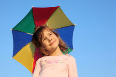 Girl with multicolor rainbow umbrella. Little girl with multicolor rainbow umbrella on blue sky Stock Images