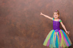 Girl in multicolor tutu pointing to brown wall royalty free stock photos