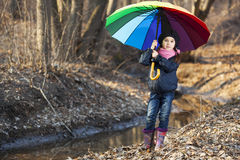 Girl with multicolored umbrella in autumn park Stock Image