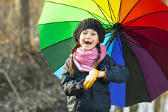 Girl with multicolored umbrella in autumn park Stock Photos