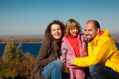 Girl with mum and daddy, in bright autumn day Stock Images