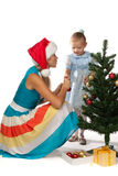 Girl with mum decorates a Christmas tree Stock Images