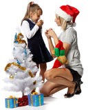 Girl with mum decorates a Christmas tree Stock Photography