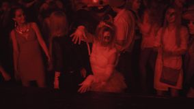 Girl in mummy zombie costume dance in crowd at night club halloween party stock video footage