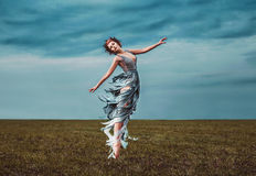 Girl muse, dancing in a field royalty free stock image