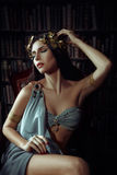 Girl muse of the poet. In Greek robes standing in the room full of books and inspiring fashion creative color toning royalty free stock image