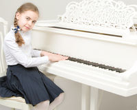 A girl from a music school plays the piano. Charming little blonde with long wattled hair in plaits, playing on a white grand piano. In musical school Royalty Free Stock Image