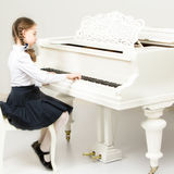 A girl from a music school plays the piano. Charming little blonde with long wattled hair in plaits, playing on a white grand piano. In musical school Stock Images