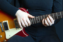 Girl musician plays on electric guitar Stock Images