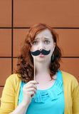 Girl with mustache party accessory Royalty Free Stock Image