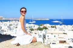 Girl in mykonos. Young caucasian woman in a white dress stiting overlooking the view of the island of mykonos Stock Image