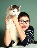 Girl in myopia glasses hug big siberian cat Royalty Free Stock Image