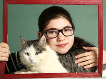 Girl in myopia glasses hug big siberian cat Royalty Free Stock Photo
