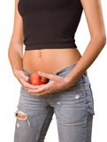Girl with naked abdomen. Close-up of young girl`s belly with an red apple in arms Royalty Free Stock Photography