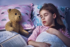 Girl is napping in the bed. Adorable little child girl is napping in the bed. Quiet sleep with teddy bear after reading book Royalty Free Stock Photos