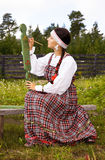 Girl in national costume paints a spinning wheel Stock Photo