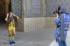 Girl in national costume posing for woman photographer Shiraz, I. Fars Province, Shiraz, Iran - 19 april, 2017: The girl photographer photographing the model in Royalty Free Stock Image