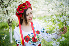 Girl in national dress among flowering branches Royalty Free Stock Photos