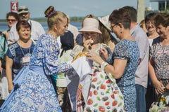 Girl in national dresses met passengers from ship Stock Image