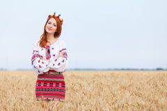 Girl in national ukrainian clothes. Redhead girl in national ukrainian clothes on the wheat field Stock Photo