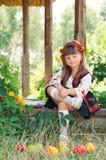 Little Ukrainian girl in national costume sitting on the porch. Girl in the national Ukrainian costume sitting in the garden with fruit Royalty Free Stock Images