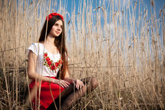 Girl in national Ukrainian costume sitting in the reeds Royalty Free Stock Images
