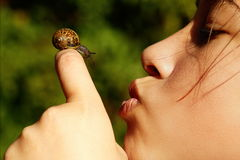 Girl and nature. Young girl blowing a kiss to a snail, nature Royalty Free Stock Photos