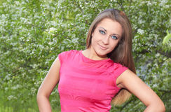 Girl on the nature. Girl in a pink dress on a background of flowering tree Royalty Free Stock Photos