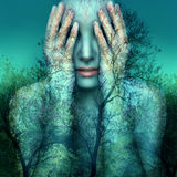 Girl and nature in blue. Surreal and artistic image of a girl who covers her eyes with her hands on a background of trees and sky Royalty Free Stock Photos