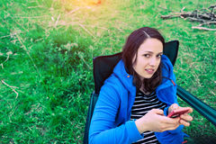 A girl in the nature looks in a mobile phone. Stock Photos
