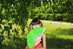 Girl on the nature of the person covers green fan Stock Images