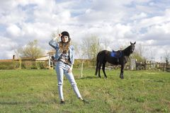 A girl in nature prepares to tame a horse stock image