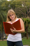 Girl on nature with a writing-book Stock Image