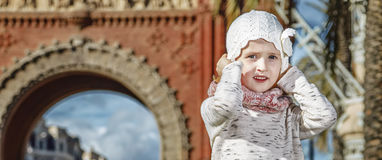 Girl near Arc de Triomf in Barcelona, Spain holding her hat. In Barcelona for a perfect winter. Full length portrait of trendy girl near Arc de Triomf in Stock Photos