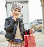 Girl near Arc de Triomphe in Paris holding French macaroon. Stylish autumn in Paris. modern girl with red present bag near Arc de Triomphe in Paris holding Royalty Free Stock Image