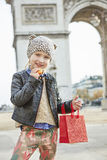 Girl near Arc de Triomphe in Paris holding French macaroon Stock Images