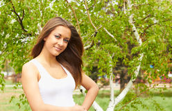 Girl near birch. Smiling girl in a white T-shirt against the backdrop of birch Royalty Free Stock Image