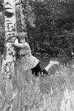 The girl near a birch. The woman leans against a birch. Monochrome Stock Images