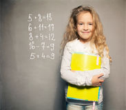 Girl near blackboard with book Stock Photo