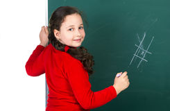 Girl  near blackboard. Smiling beauty girl with pigtail standing near blackboard and holding chalk, look at camera Stock Image
