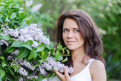 Girl near blossoming lilac Royalty Free Stock Image