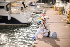 Beautiful girl outdoors. Spring day. The girl near boats on a marina stock image