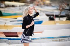 Beautiful girl outdoors. Spring day. The girl near boats on a marina royalty free stock photo