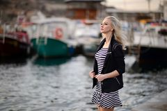 Beautiful girl outdoors. Spring day. The girl near boats on a marina royalty free stock photos