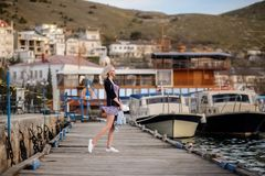 Beautiful girl outdoors. Spring day. The girl near boats on a marina stock photography