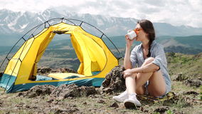 Girl near bonfire. Travel, tourism, camping - young slim sporty woman tourist brunette at the beautiful nature landscape. Sitting near the tent by the fire stock footage