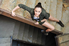 Girl near the brick wall in military style. Royalty Free Stock Images