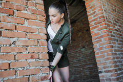 Girl near the brick wall in military style. Royalty Free Stock Image