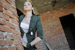 Girl near the brick wall in military style. Royalty Free Stock Photos