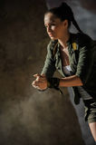 Girl near the brick wall in military style. Royalty Free Stock Photo
